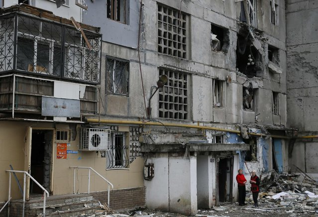 Women stand near a multi-storey block of flats damaged by shelling in Yenakieve town, northeast from Donetsk, February 2, 2015. (Photo by Maxim Shemetov/Reuters)