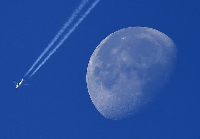 A passenger plane is seen with the moon behind over west London, Britain, October 2, 2015. (Photo by Toby Melville/Reuters)