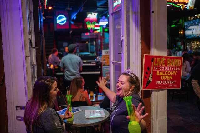 """Trisha Denham and her best friend Meshanna Cason, both of Dallas, sing along to Garth Brook's """"Friends in Low Places"""" as they listen to live music after the coronavirus disease (COVID-19) restrictions were eased in New Orleans, Louisiana, U.S., March 13, 2021. (Photo by Kathleen Flynn/Reuters)"""