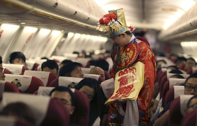 A flight attendant (C) dressed as Cai Shen, or the God of Wealth, speaks to a passenger during a promotional event to celebrate the upcoming Chinese Lunar New Year, on a Lucky Air flight travelling from Hangzhou of Zhejiang province to Kunming of Yunnan province, February 8, 2015. (Photo by Wong Campion/Reuters)