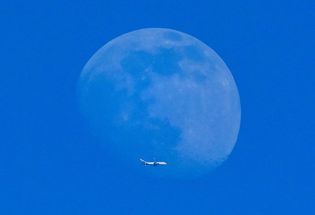 The silhouette of an airplane is seen in front of the moon in Moscow on March 25, 2021. (Photo by Yuri Kadobnov/AFP Photo)