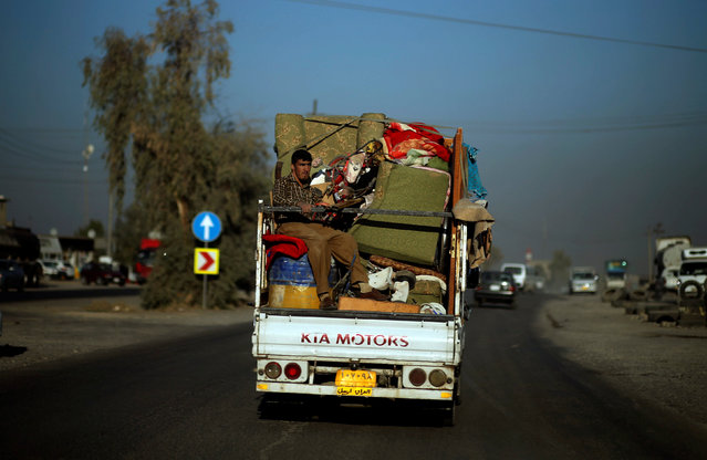 A newly displaced Iraqi rides on the back of a truck while fleeing the Islamic State stronghold of Mosul, Iraq November 29, 2016. (Photo by Mohammed Salem/Reuters)