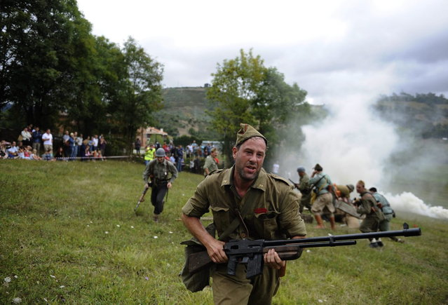 """An actor takes part in a re-enactment of the """"Battle of Areces"""" that took place during the Spanish Civil War, in Grullos, north of Spain, September 14, 2013. The re-enactment of the historic 1937 battle was organised by the Frente del Nalon Association. (Photo by Eloy Alonso/Reuters)"""