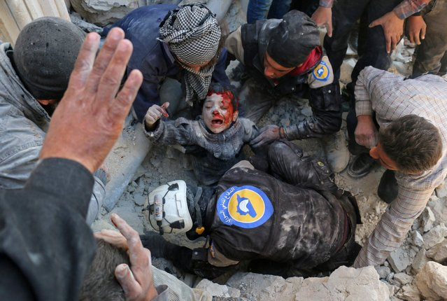Syrian civil defence volunteers, known as the White Helmets, rescue a boy from the rubble following a reported barrel bomb attack on the Bab al- Nairab neighbourhood of the northern Syrian city of Aleppo on November 24, 2016. (Photo by Ameer Alhalbi/AFP Photo)