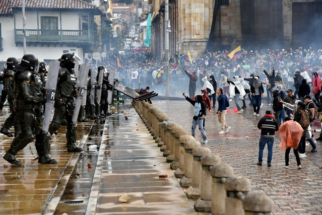 Protesters throw objects and shout to riot police officers at Bolivar square during the national strike against the tax reform proposed by Duque's administration on April 28, 2021 in Bogota, Colombia. Unions joined to call to a national strike and demonstrations in major cities, urging participants to follow COVID-19 protocols. They seek to sink a tax reform which proposes elimination of VAT free goods. As the third wave of COVID hits the country, Colombia sets new records of deaths per day. (Photo by Guillermo Legaria/Getty Images)