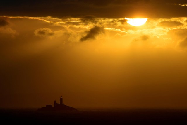 The Godrevy Lighthouse is seen just after sunrise, in St Ives Bay, Cornwall, southwest Britain on May 25, 2021. (Photo by Toby Melville/Reuters)