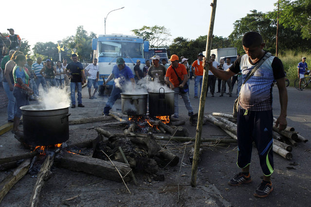 People cook in the streets during a protest due to a lack of cash in El Pinal, Venezuela December 16, 2016. (Photo by Carlos Eduardo Ramirez/Reuters)
