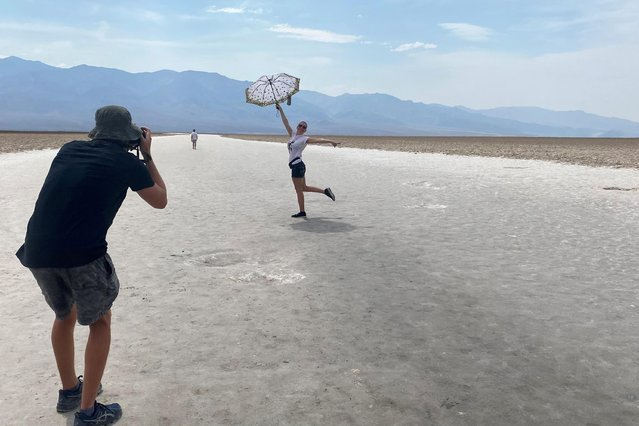 43-year-old Lana, a tourist from North Carolina poses for a picture holding an umbrella at Badwater Basin, the lowest point of North America below sea level in Death Valley, California, U.S. June 16, 2021. (Photo by Norma Galeana/Reuters)