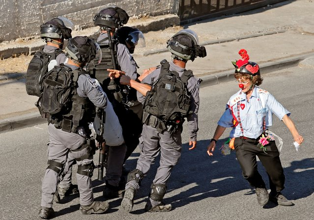 An Israeli activist dressed as a clown runs around security forces as they arrest a protester near a police checkpoint at the entrance of the Sheikh Jarrah neighbourhood in east Jerusalem, on June 25, 2021. Tensions between Israel and Palestinians that lead to 11 days of military violence last month, initially flared in the Sheikh Jarrah neighbourhood where Israeli police cracked down on people protesting the planned expulsion of Palestinian families from their homes so Jewish settlers could move in. (Photo by Ahmad Gharabli/AFP Photo)