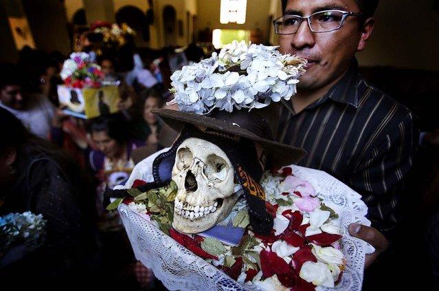 "A man holds a skull during the ""Dia de los natitas"" ceremony. (Photo by David Mercado/Reuters))"
