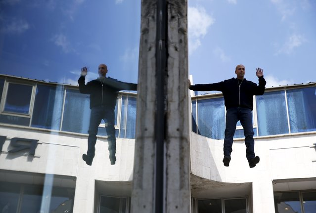 "Israeli illusionist and endurance artist Hezi Dean performs a purported levitation trick in Tel Aviv March 22, 2015. Dean on Sunday began what he calls a ""24-hour levitation"" on the outside of a Tel Aviv building. (Photo by Baz Ratner/Reuters)"