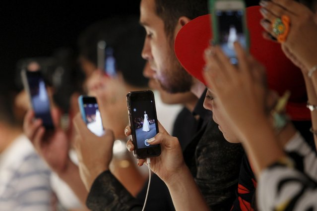 The audience takes pictures with their mobile phones during the show of Peruvian designer Claudia Jimenez at Lima Fashion Week March 24, 2015. (Photo by Enrique Castro-Mendivil/Reuters)