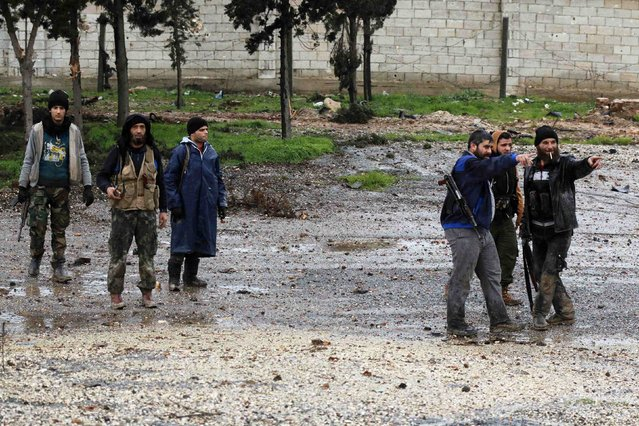 Rebel fighters carry their weapons as they stand at al-Breij frontline, after what they said was an advance in the area by them and they took control of factories where forces loyal to Syria's President Bashar al-Assad were stationed, in Aleppo January 5, 2015. (Photo by Hosam Katan/Reuters)