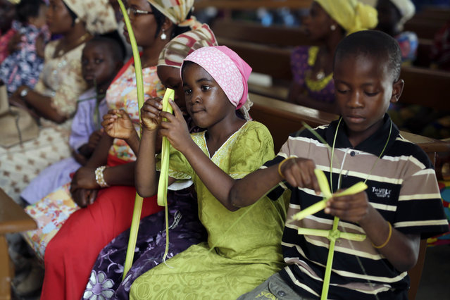 Nigerian children make crosses from palms during Palm Sunday service at the Our Lady of the Apostles catholic church in Kaduna, Nigeria Sunday, March 29, 2015. Nigerians are going to the polls to vote in presidential elections. Nigerian officials say voting continued in some areas on Sunday because of technical problems. (Photo by Jerome Delay/AP Photo)
