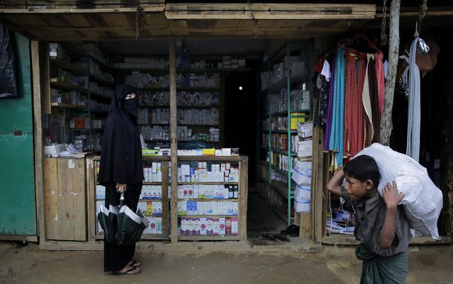 In this photograph taken August 28, 2018, a Rohingya woman waits for the shopkeeper to show up at a makeshift pharmacy in Kutupalong refugee camp, Bangladesh. Faith healers have long been sought out in Rohingya society to treat physical and mental ailments. Their trade has thrived in part because of traditional beliefs and in part because Rohingya have lacked access to modern medical care in Buddhist-majority Myanmar, where they are one of the most persecuted minority groups in the world. Access to medical care has changed for the better in the refugee camps in Bangladesh, yet many Rohingya still seek out their faith healers. (Photo by Altaf Qadri/AP Photo)