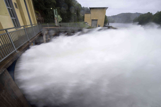 Water shoots out of the outlet of the hydroelectric power station below the Ruhr dam near Heimbach, Germany, Friday, July 16, 2021. (Photo by Lino Mirgeler/dpa via AP Photo)