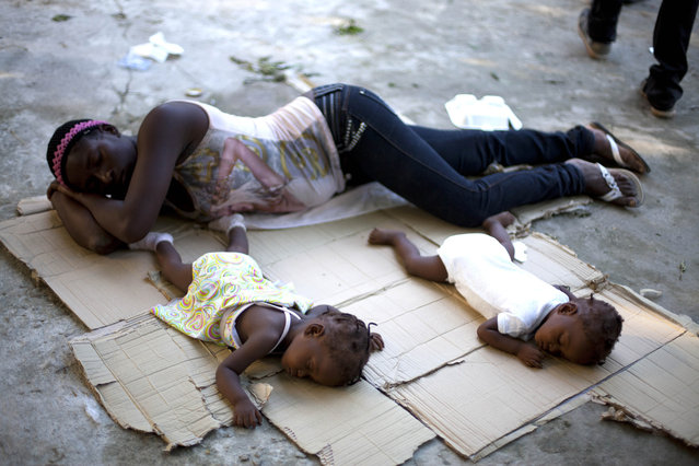 Marie Matte Mayan 26, sleeps on the floor with her twins, Maudeline and Maudena Pierre an a shelter after being deported by Dominican Republic authorities, in Croix-des-Bouquets, Haiti, Sunday November 24, 2013. Dominican authorities expelled 244 Haitians after an elderly Dominican couple was slain in an apparent burglary near the border between the two countries and an angry mob retaliated by killing a Haitian man, Rev. Antoine Lissaint of Haiti's Jesuit Refugee and Migrant Organization said Sunday. (Photo by Dieu Nalio Chery/AP Photo)