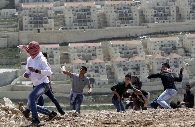 Palestinian protesters throw stones toward Israeli army soldiers in front of the Israeli settlement of Beitar Illit during clashes that erupted following a protest marking Land Day, in the village of Wadi Fukin, near the West Bank city of Bethlehem, Monday, March 30, 2015. Land Day commemorates riots on March 30, 1976, when six people were killed during a protest by Israeli Arabs whose property was annexed in northern Israel to expand Jewish communities. (Photo by Mahmoud Illean/AP Photo)