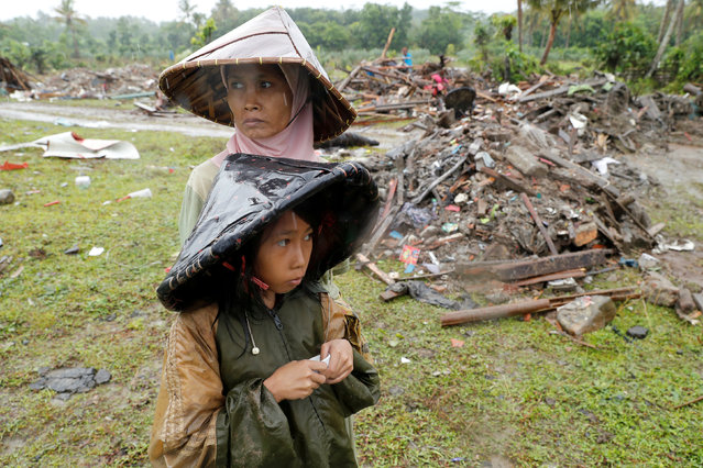 A woman and child are seen next to debris after a tsunami in Sumur, Banten province, Indonesia on December 26, 2018. (Photo by Jorge Silva/Reuters)