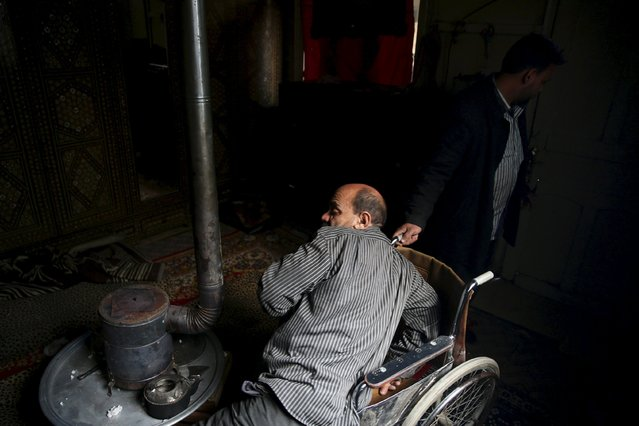 Shahrour, 54, whose leg was amputated due to complications from diabetes, attempts to sit on his wheelchair at his home in the besieged town of Arbeen, in the Damascus suburbs, Syria February 6, 2016. (Photo by Bassam Khabieh/Reuters)