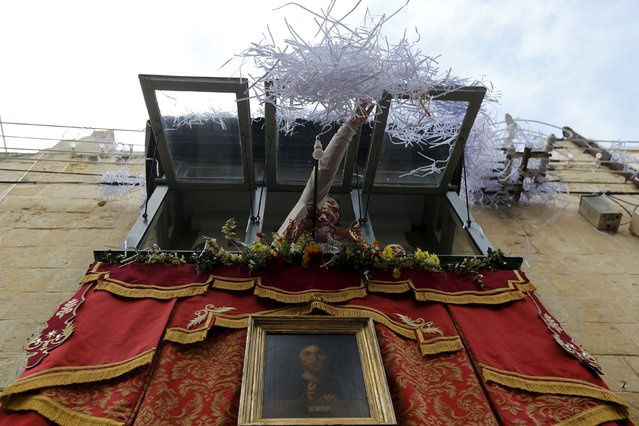 A woman pushes confetti off her balcony window during an Easter Sunday procession in Cospicua, outside Valletta April 5, 2015. (Photo by Darrin Zammit Lupi/Reuters)