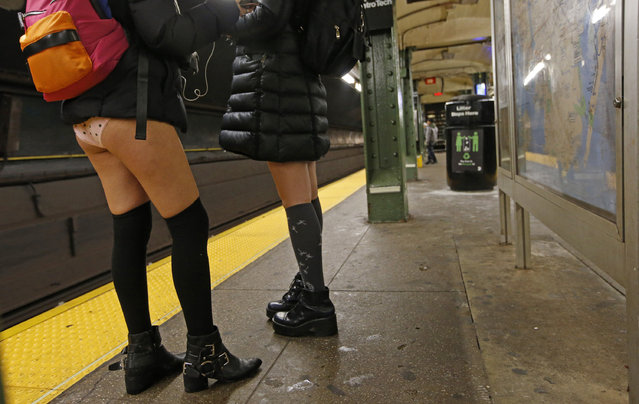 Two pantless women wait for a train at Brooklyn's Jay Street/MetroTech station during the 16th annual No Pants Subway Ride, Sunday, January 8, 2017, in New York. Created in 2002 by Charlie Todd of Improv Everywhere, the group aims to surprise and delight random strangers through positive pranks. (Photo by Kathy Willens/AP Photo)