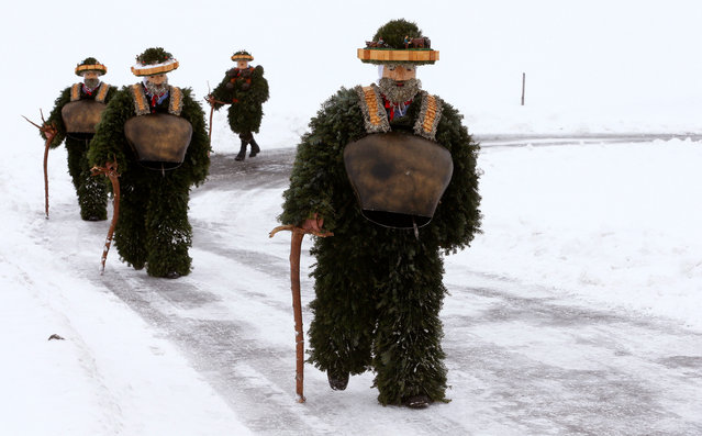 """Men dressed as """"Chlaeuse"""", figures that scare away evil spirits, carry round bells and cowbells as they walk on a partially snow-covered road during the traditional """"Sylvesterchlausen"""" near the northeastern village of Urnaesch, Switzerland January 13, 2017. (Photo by Arnd Wiegmann/Reuters)"""