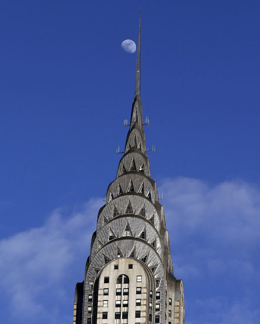 The moon is seen high above the Chrysler Building in midtown Manhattan in New York, USA, 30 March 2015. The Chrysler Building is an Art Deco style skyscraper built in 1928 and was finished in 1930. The building is owned by the Abu Dhabi Investment Council. (Photo by Jason Szenes/EPA)