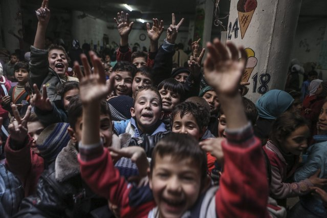 A photograph made available on 21 February 2016 shows Syrian children in a school in the Al-Qaboun neighbourhood of Damascus, Syria, 20 February 2016. The area is controlled by forces opposing the Syrian regime with which they brokered a ceasefire. (Photo by Mohammed Badra/EPA)