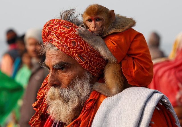 "A Sadhu or a Hindu holy man carrying his pet monkey walks after taking a dip at the confluence of the river Ganges and the Bay of Bengal on the occasion of ""Makar Sankranti"" festival at Sagar Island, south of Kolkata, India, January 14, 2017. (Photo by Rupak De Chowdhuri/Reuters)"