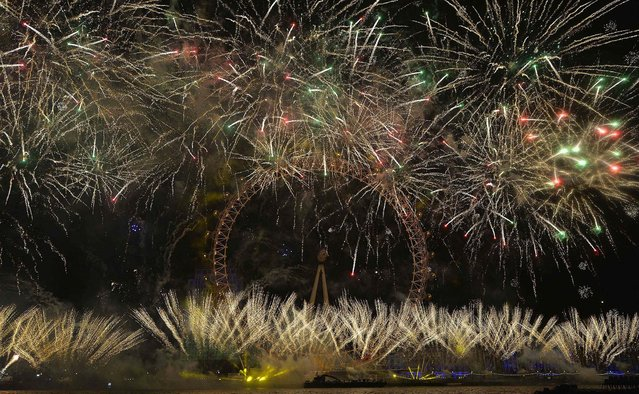 Fireworks explode around the London Eye wheel during New Year celebrations in London. (Photo by Toby Melville/Reuters)
