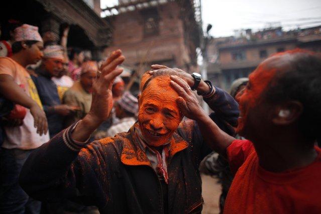 A Nepalese man, right, smears vermillion powder on his friend during Sindur Jatra festival in Thimi, outskirts of Kathmandu, Nepal, Wednesday, April 15, 2015. (Photo by Niranjan Shrestha/AP Photo)