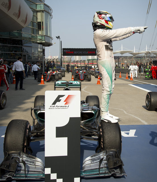 Mercedes driver Lewis Hamilton of Britain stands atop his car after winning the Chinese Formula One Grand Prix at Shanghai International Circuit in Shanghai, China, Sunday, April 12, 2015. (Photo by Mark Schiefelbein/AP Photo)