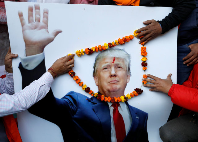 Members of Hindu Sena, a right-wing Hindu group, place a garland on an poster of U.S President-elect Donald Trump ahead of his inauguration, in New Delhi, India January 19, 2017. (Photo by Cathal McNaughton/Reuters)