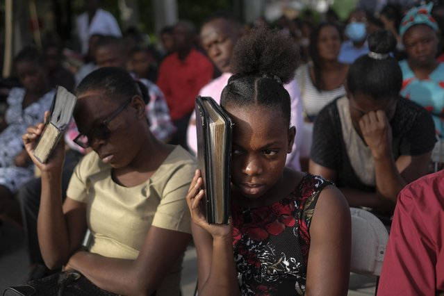 Parishioners attend a mass on the grounds next to an earthquake-damaged church in Les Cayes, Haiti, Sunday, August 22, 2021, eight days after a 7.2 magnitude earthquake hit the area. (Photo by Matias Delacroix/AP Photo)