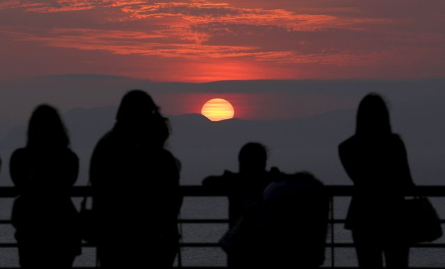 People watch the sunset on a terrace at Larcomar shopping mall in the Miraflores district of Lima April 17, 2015. (Photo by Mariana Bazo/Reuters)