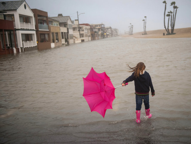 Isabella Busse, 6, walks through floodwater near the Seal Beach Pier during a storm in Seal Beach, Calif., Sunday, January 22, 2017. The heavy downpour on Sunday drenched Orange County in one of the heaviest storms of the year. Fast-moving floodwaters swept through California mountain communities and residents fled homes below hillsides scarred by wildfires as the third in the latest series of storms brought a deluge Sunday and warnings about damaging mudslides. (Photo by Ana Venegas/The Orange County Register via AP Photo)
