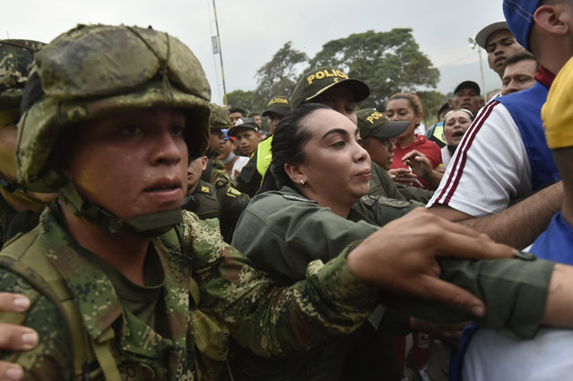 Colombian police officers escort a female member of Venezuela's Bolivarian National Armed Forces (FANB) (C) who deserted, near the Simon Bolivar international bridge in Cucuta, Colombia, on February 23, 2019. Venezuela braced for a showdown between the military and regime opponents at the Colombian border on Saturday, when self-declared acting president Juan Guaido has vowed humanitarian aid would enter his country despite a blockade. (Photo by Luis Robayo/AFP Photo)
