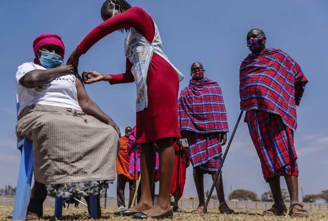 Maasai men queuing to receive the AstraZeneca coronavirus vaccine look over as a woman, who is not, Maasai receives a jab at a clinic in Kimana, southern Kenya Saturday, August 28, 2021. Plans for COVID-19 booster shots in some Western countries are highlighting vast disparities in access to vaccines around the world. (Photo by Brian Inganga/AP Photo)