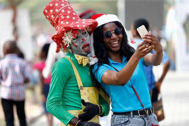 A picnicker takes a selfie with a man dressed as clown at an amusement park, on Boxing Day, in ikeja district in Nigeria's commercial capital Lagos, December 26, 2016. (Photo by Aintunde Akinleye/Reuters)