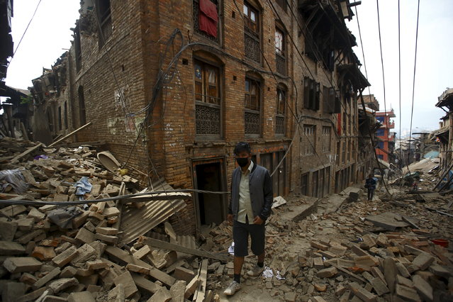 A man walks along damaged houses a day after an earthquake in Bhaktapur, Nepal April 26, 2015. (Photo by Navesh Chitrakar/Reuters)