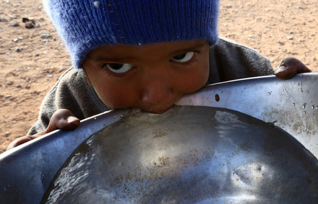 A stateless Arab boy from an ethnic group known as Bedoon, who are believed to be descendants of nomadic Bedouins, drinks water from a pot in a desert west of Al-Jawf region, Saudi Arabia, December 31, 2016. (Photo by Mohamed Al Hwaity/Reuters)