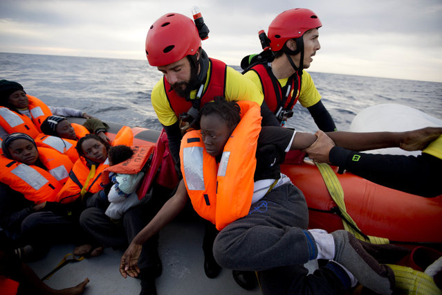 A woman is assisted by members of the Spanish NGO Proactiva Open Arms, as they crowd on board of a rubber boat sailing out of control in the Mediterranean some miles north of Sabratha, Libya, on Friday, February 3, 2017. European Union leaders are poised to take a big step on Friday in closing off the illegal migration routes from Libya across the central Mediterranean, where thousands have died trying to reach the EU, the EU foreign affairs chief Federica Mogherini said. (Photo by Emilio Morenatti/AP Photo)