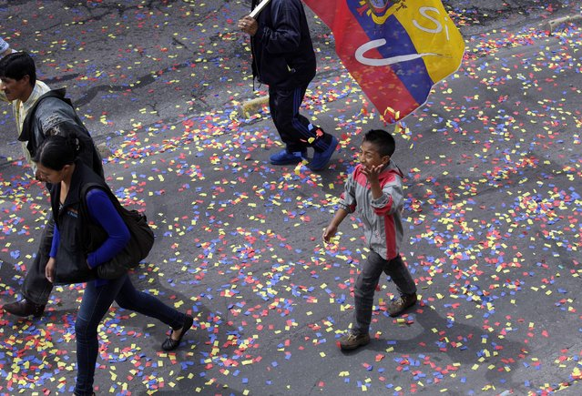 Confetti litters the parade route as workers take part in the May Day parade in Quito, Ecuador, Friday, May 1, 2015. (Photo by Dolores Ochoa/AP Photo)