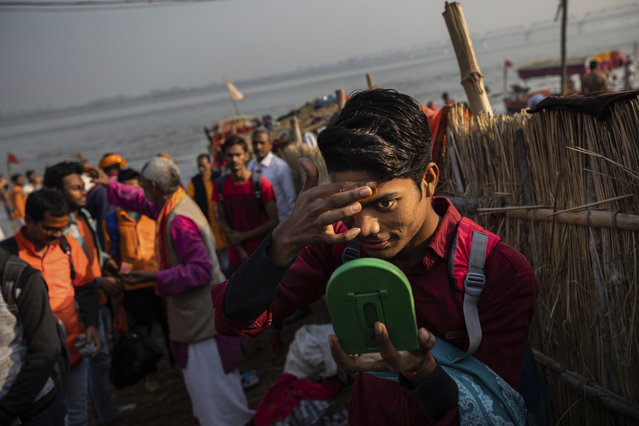 In this Sunday, November 25, 2018 photo, a Hindu hardline supporter applies saffron to his forehead in Ayodhya, Uttar Pradesh, India. As with similar movements across the world, Hindu nationalism, once fringe, has now taken a central place in India's politics. (Photo by Bernat Armangue/AP Photo)