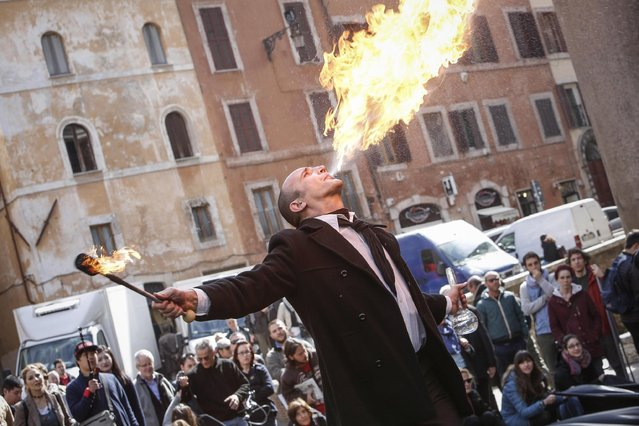 A fire-breather entertains participants of a flash mob called in support of a referendum on offshore oil and gas drilling in Italy, at the Pantheon monument in Rome, Italy, March 18, 2016. The referendum will be on April 17, 2016. (Photo by Giuseppe Lami/EPA)