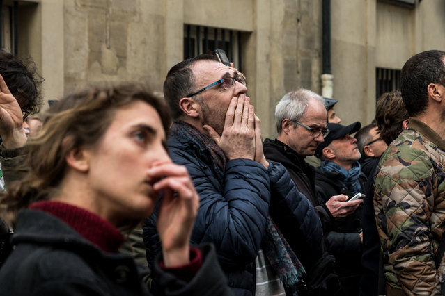 People watch the landmark Notre-Dame Cathedral burning in central Paris on April 15, 2019. (Photo by Nicolas Liponne/NurPhoto via Getty Images)
