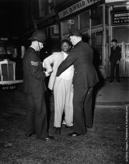 London police search a black youth in Talbot Road, Notting Hill during race riots, 1958