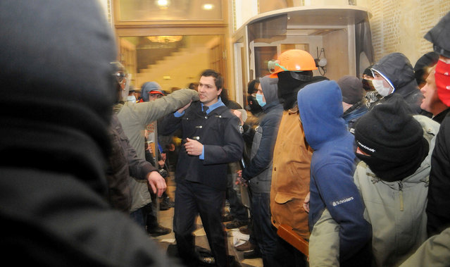 A policeman, center, tries to stop Ukrainian protesters as they seize police headquarters in Lviv, western Ukraine, early Wednesday, February 19, 2014. The violence on Tuesday was the worst in nearly three months of anti-government protests that have paralyzed Ukraine's capital, Kiev, in a struggle over the identity of a nation divided in loyalties between Russia and the West, and the worst in the country's post-Soviet history. (Photo by Pavlo Palamarchuk/AP Photo)