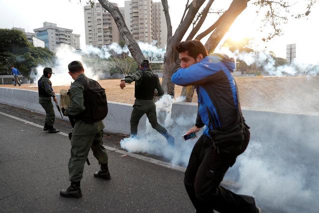 "Military members react to tear gas, near the Generalisimo Francisco de Miranda Airbase ""La Carlota"", in Caracas, Venezuela April 30, 2019. (Photo by Carlos Garcia Rawlin/Reuters)"